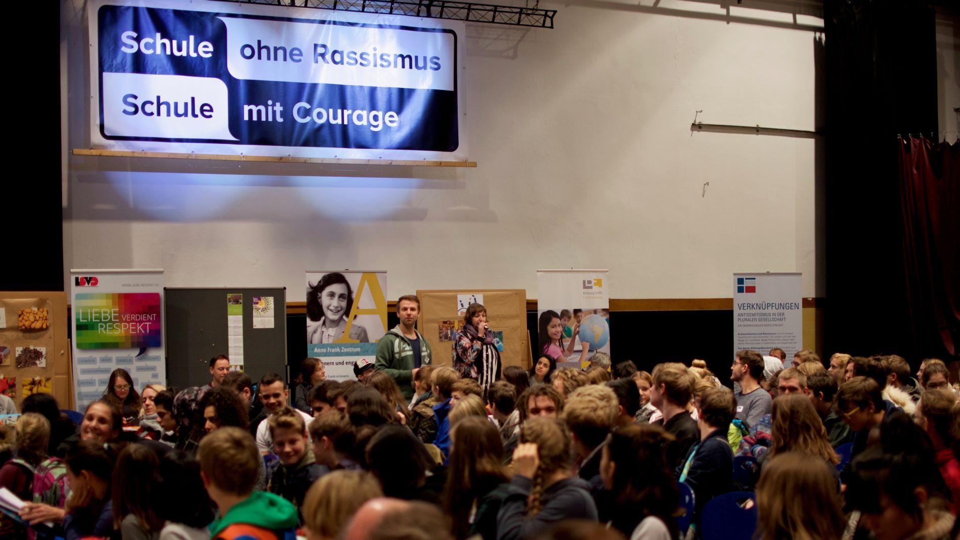 Ein voller Saal beim Landestreffen. An der Wand hängt ein Banner mit dem Logo des Courage-Netzwerks