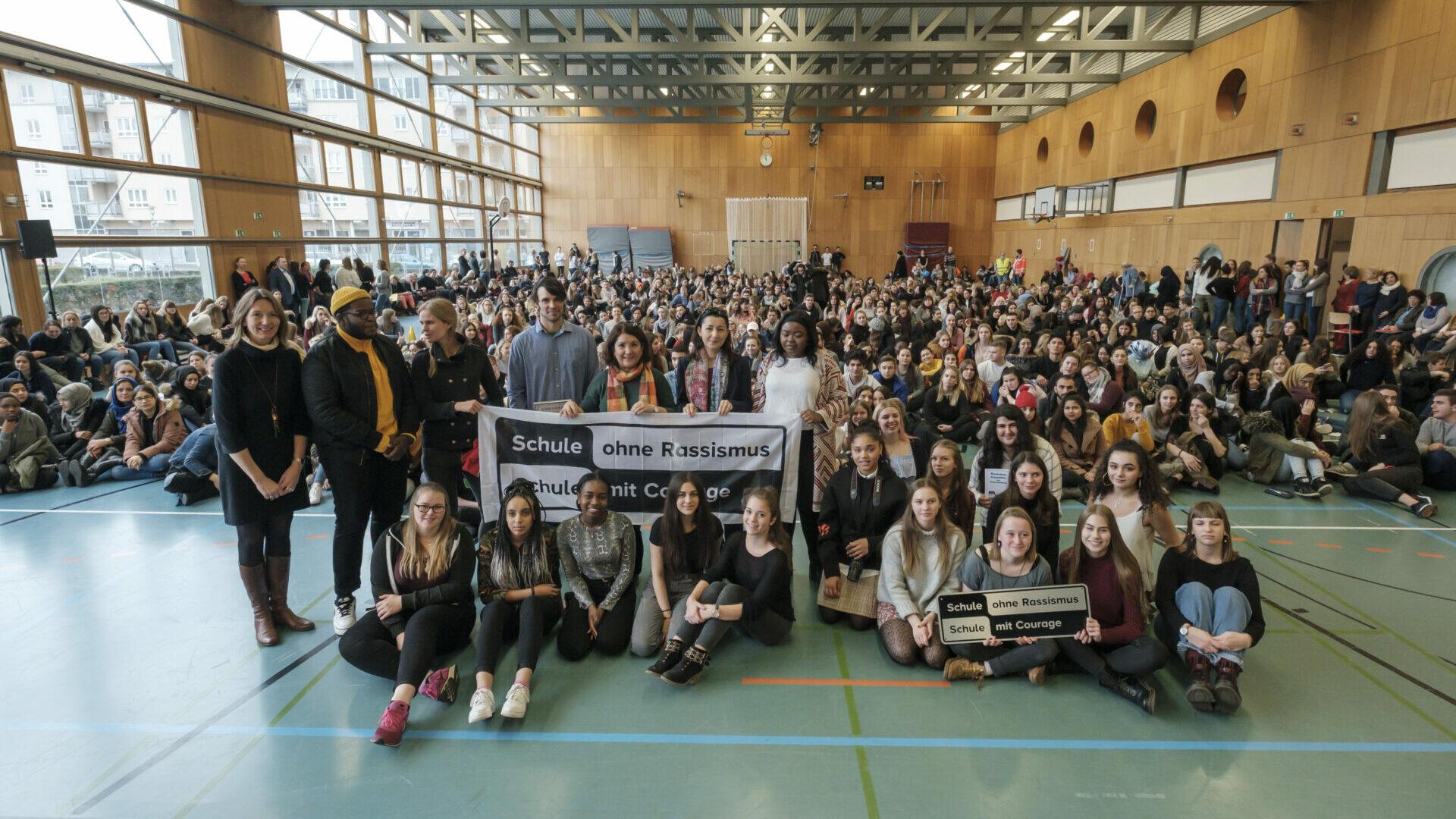 Eine Große Gruppe von Menschen in der Trunhalle einer Schule bei der Titelverleihung