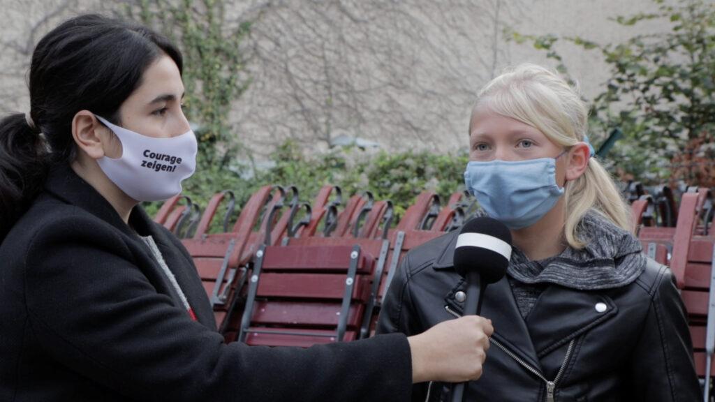 Zwei Schülerinnen im Interview. beide tragen masken. Auf der einen ist Courage zeigen lesbar.