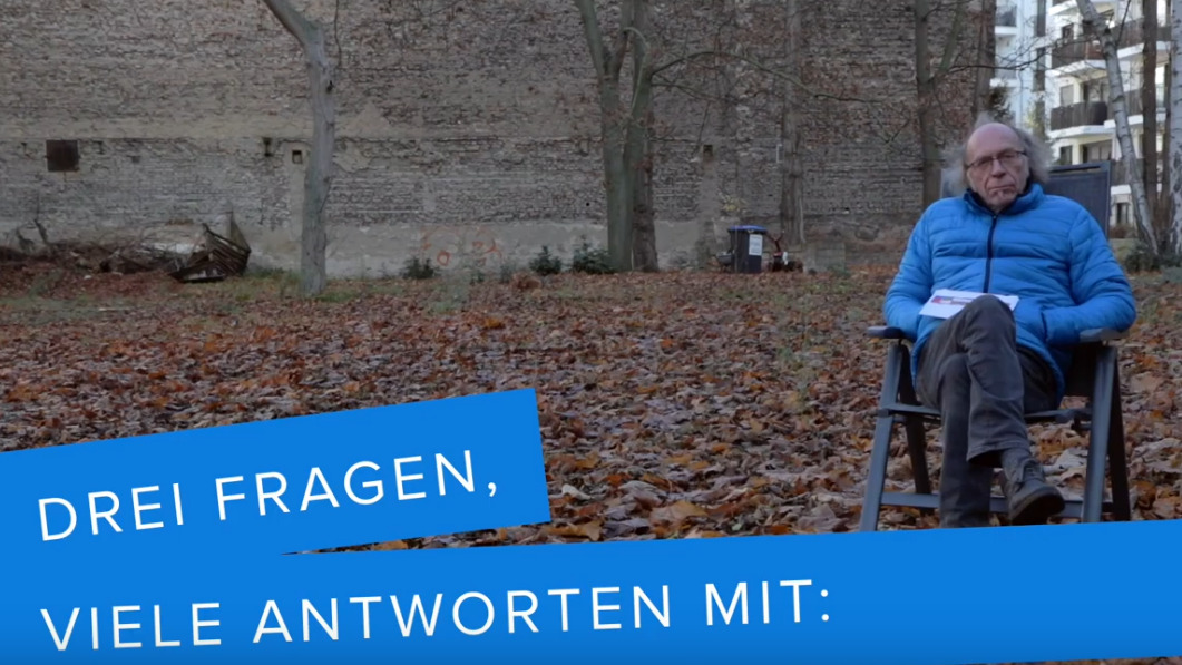 """Ein Mann sitz auf einem Stuhl auf einem leeren von Laub bedeckten Gelände. Ein Banner ist eingeblendet auf dem """"Drei Fragen vile Antworten"""" steht."""