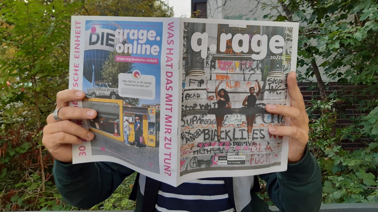 Eine Person liest in der q.rage Zeitung. Das Gesicht ist durch die Zeitung verdeckt.