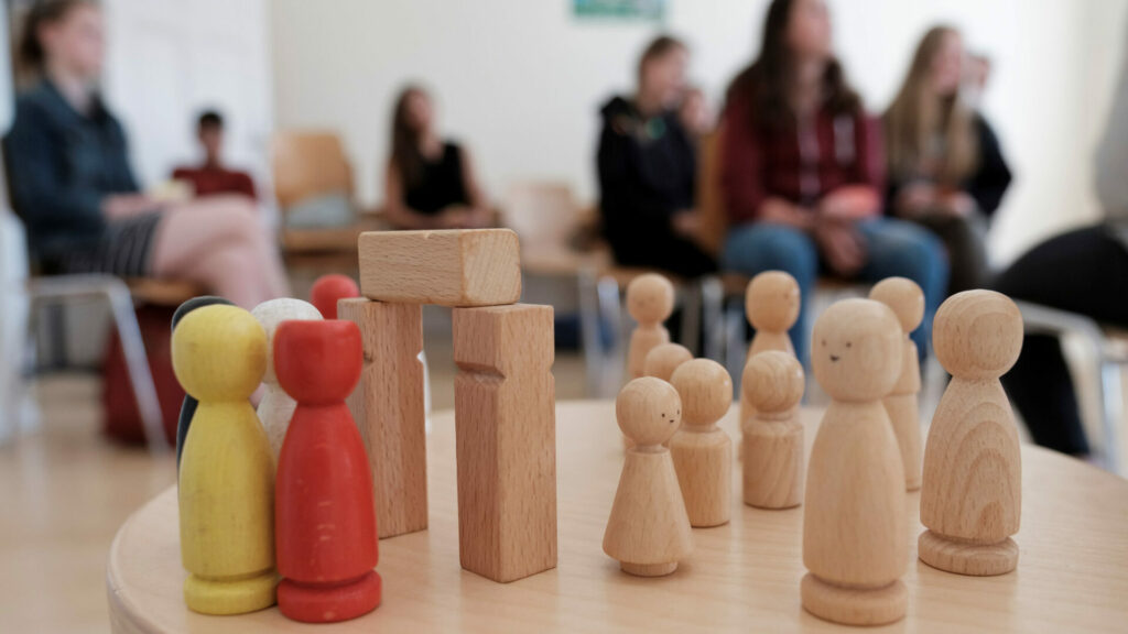 Im Vordergrund eine Gruppe von Holzfiguren im Hintergund Jugendliche in einer Workshopsituation