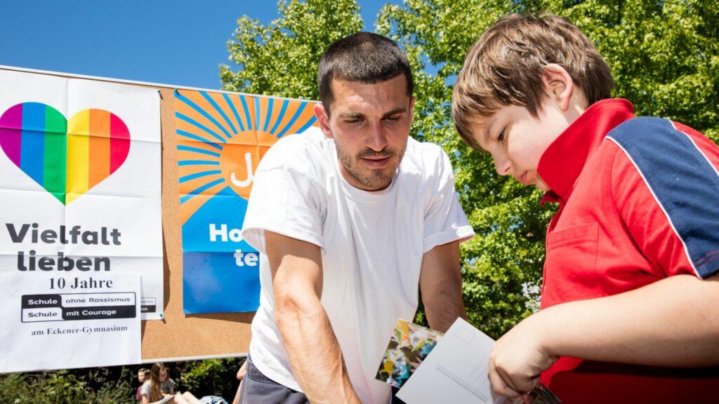 """Ein junger Mann und ein kind schauen gemeinsam auf einen Flyer, im hintergund ein """"Vielfalt lieben"""" Plakat"""