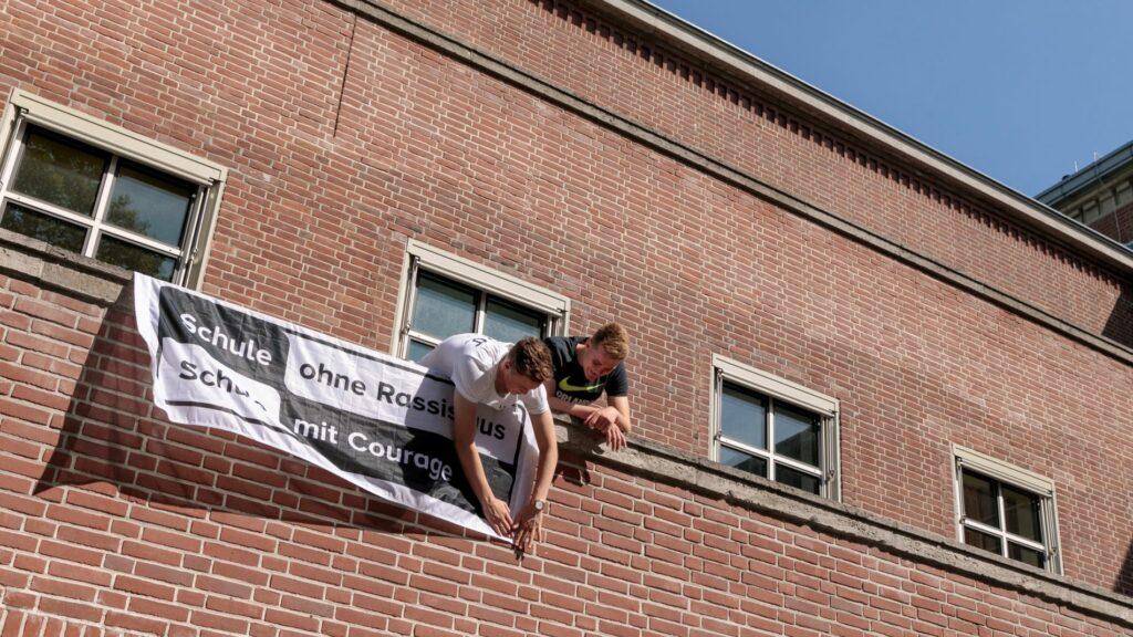 Zwei Schüler hängen ein SOR-SMC-Banner an ihrem Schulgebäude auf