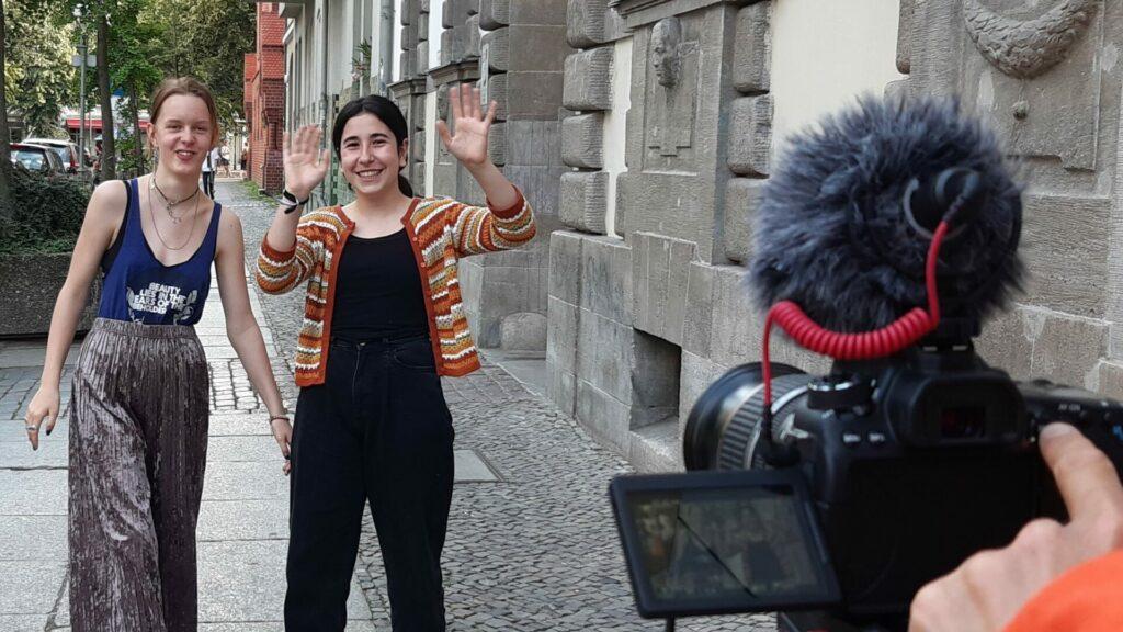 Zwei Courage Reporter*innen stehen auf der Straße vor der Kamera