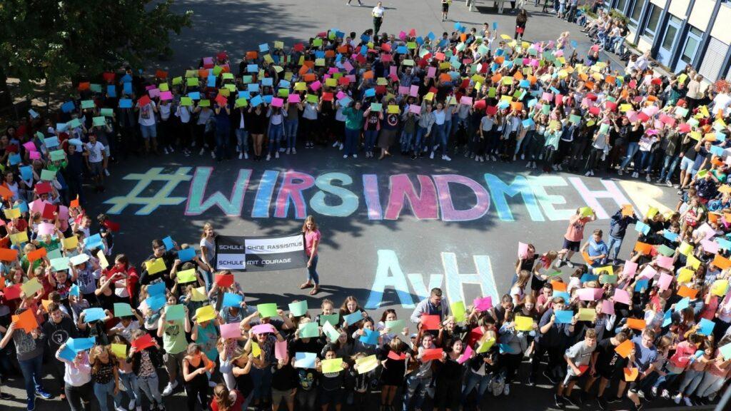 """Eine große Menschengruppe im Freien ist um einen """"Wir sind mehr""""-Schriftzug auf dem Boden versammelt"""