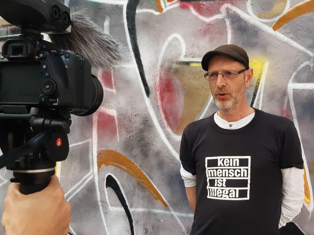 """Eine Person die ein Tshirt mit der Aufschrift """"Kein Mensch ist illegal"""" wird vor einer Graffiti-Wand mit einer Kamera interviewt"""