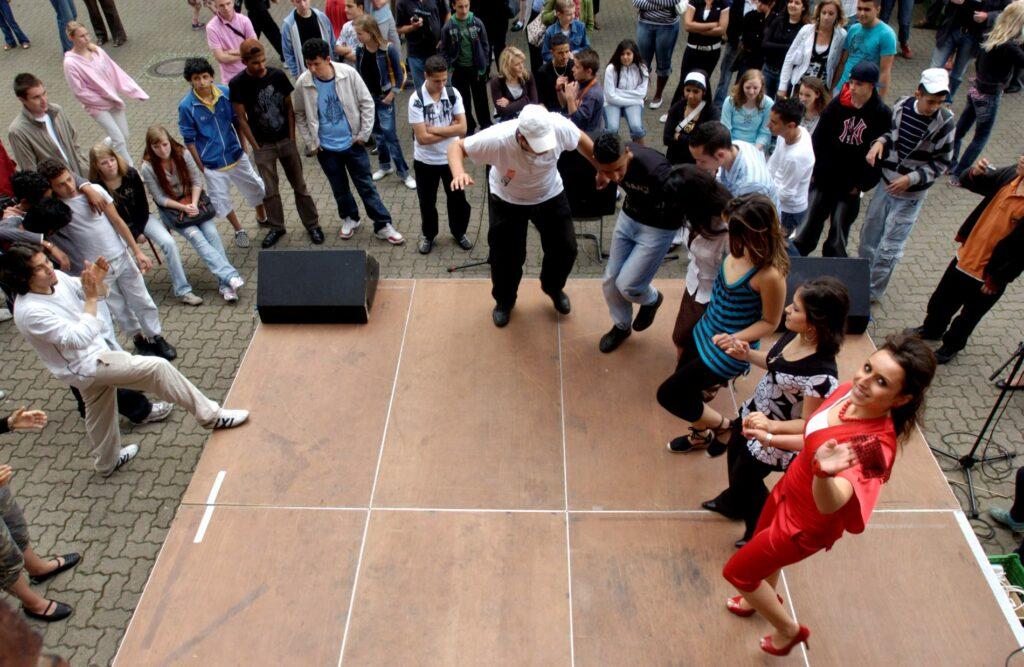 Eine Gruppe von Schüler*innen tanzt umarmt auf einer Bühne