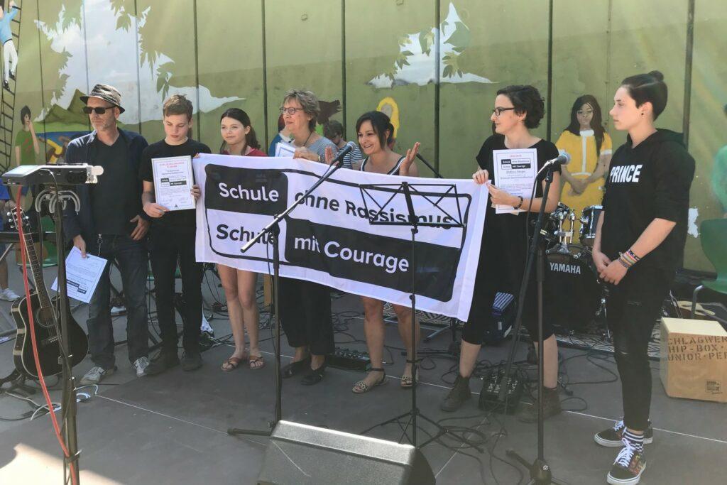 Eine Gruppe von Schulmitgliedern im Freien mit dem SOR-SMC Banner