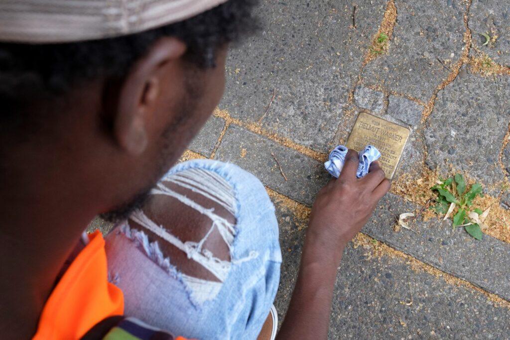 Ein* junge*r Schüler*in putzt einen Stolperstein