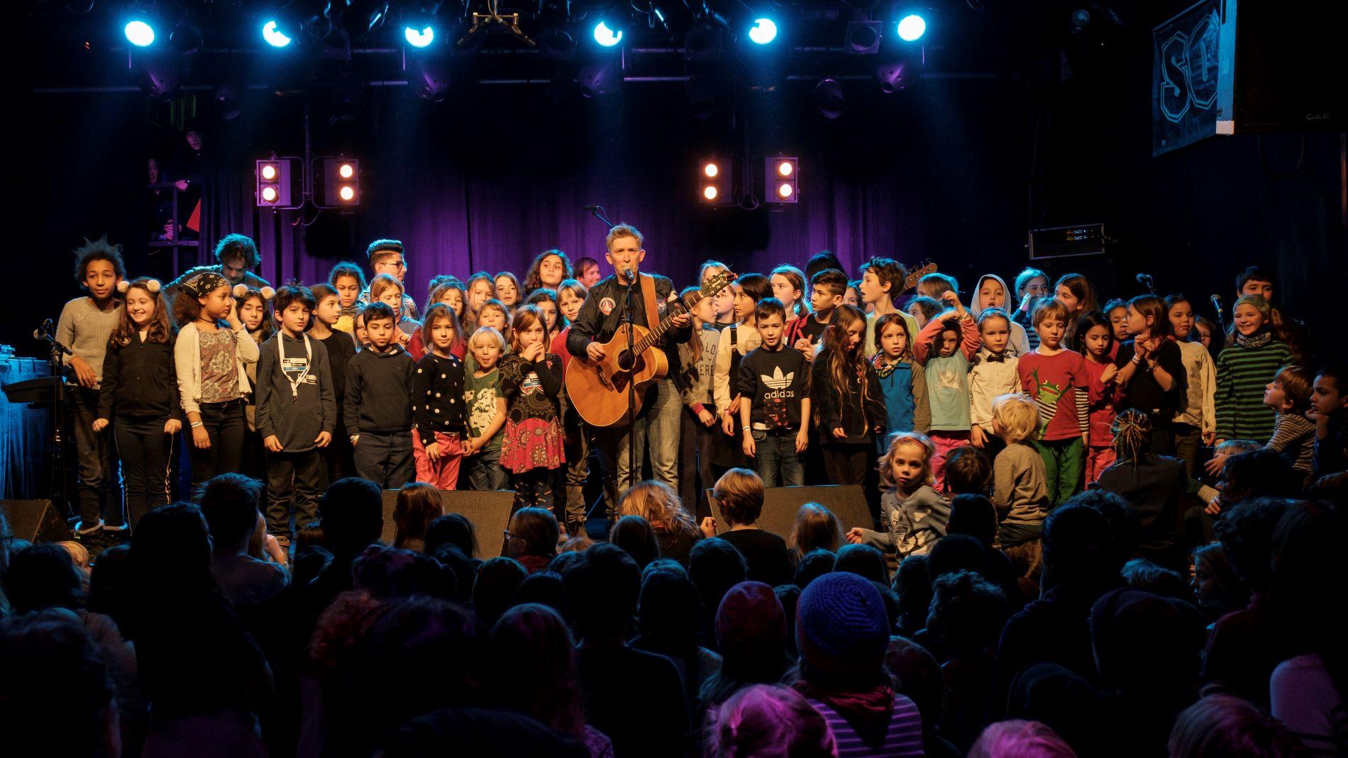Eine Konzertsituation mit vielen Schüler*innen auf der Bühne und im Zuschauerraum