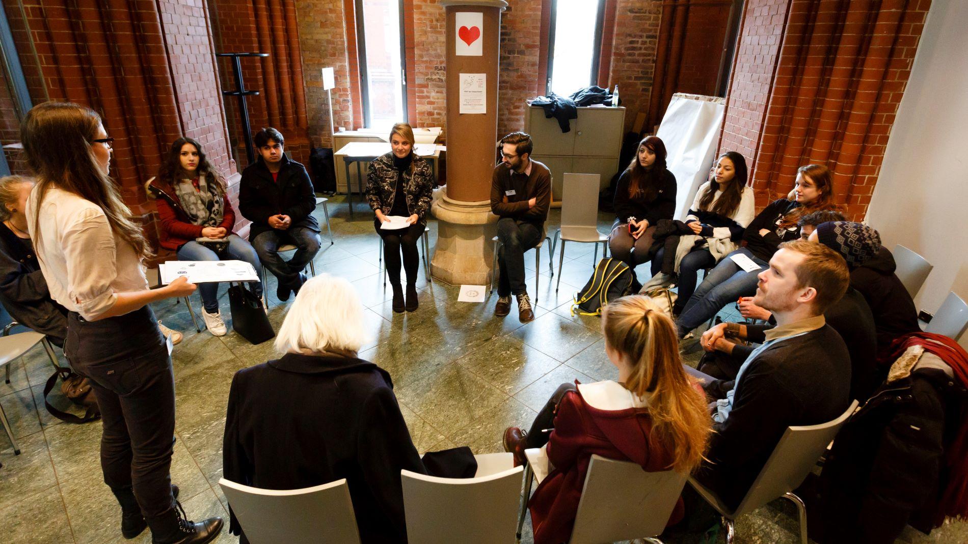 Eine Gruppe sitz im Kreis bei einem Workshop
