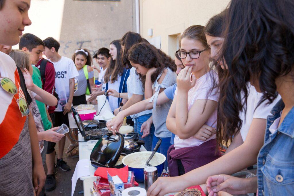 Eine Gruppe von Schüler*innen steht um einen Tisch, auf dem sie Essen zubereiten