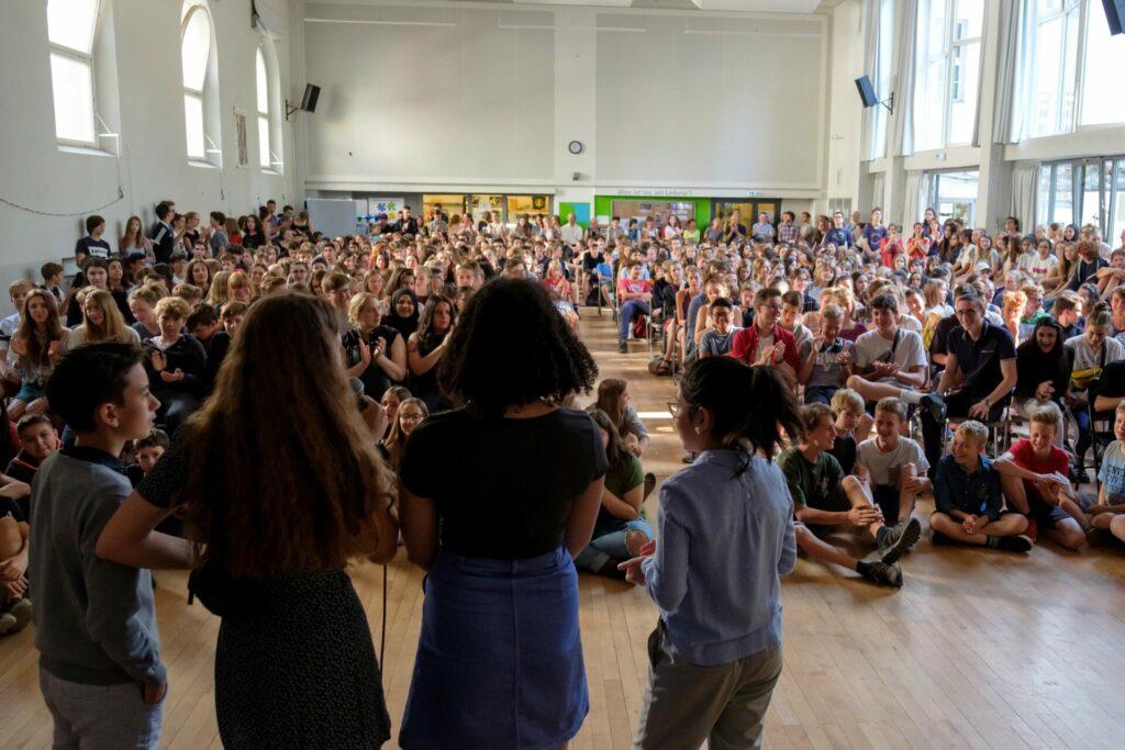 Schulmitglieder bei einer Titelverleihung in der Aula einer Berliner Schule
