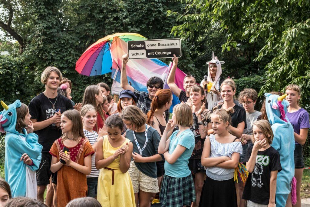Eine gruppe von Schulmitgliedern feiert die Titelverleihung an ihrer Schule