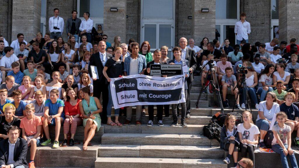 Eine große Menschengruppe bei einer Titelverleihung, die den SOR-SMC Banner hochhält
