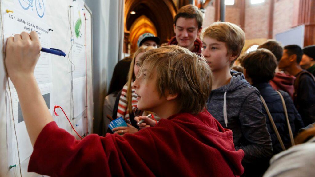 Schüler*innen beim Eintragen in Workshoplisten bei einen SOR-SMC Vernetzungstreffen