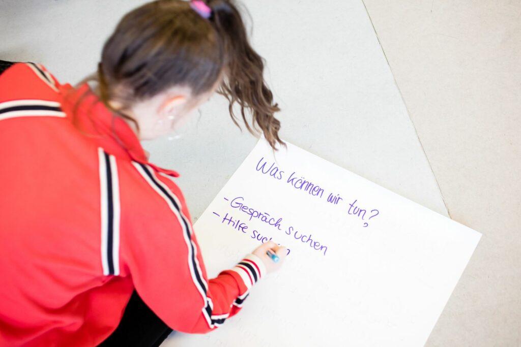 Eine Schülerin schreibt auf einem großen Blatt Papier auf dem Boden
