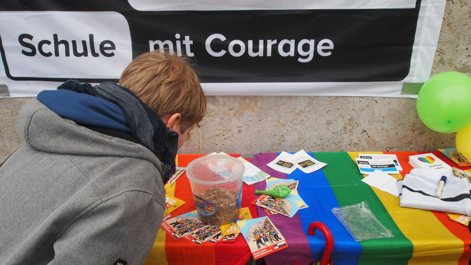 Infotisch von SOR-SMC mit Regenbogendecke. Davor ein Schüler in Rückenansicht.