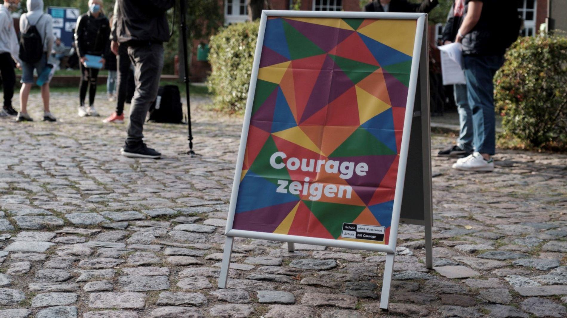 Ein Aufsteller mit einenm Plakat mit der Aufschrift Courage Zeigen