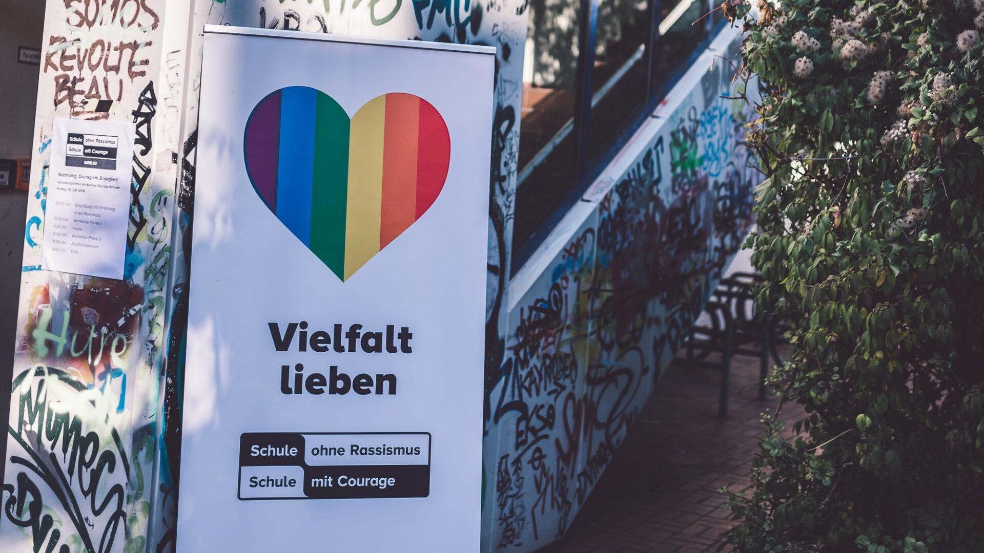 Ein Plakat mit der Aufschrift Vielfalt Lieben hängt vor einem Schulhaus