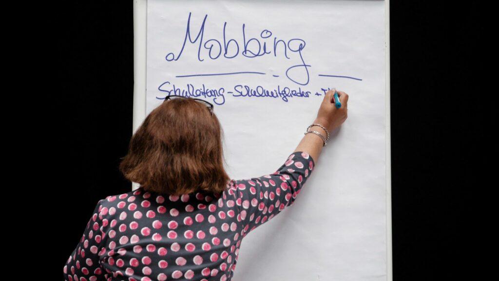 Eine Pinwand auf der eine mit dem Rücken zu uns stehende Person gerade Mobbing schreibt